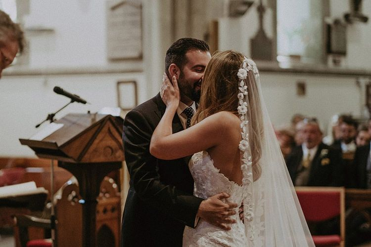 Bride and groom say 'I do' at a church ceremony in the Isle of Wight wearing a lace edge veil and strapless lace dress