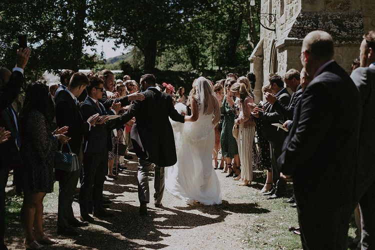 Bride wearing a lace edge veil and strapless lace wedding dress leaves the church with groom in three piece suit