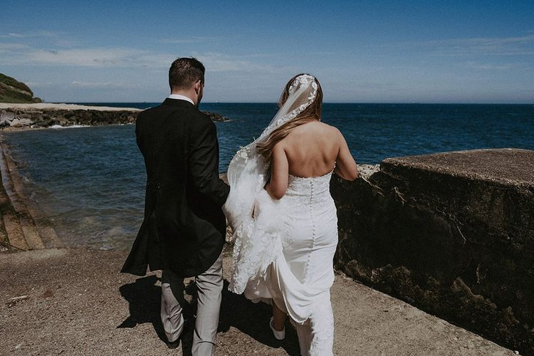 Bride and Groom enjoying the seafront in lace edge veil and strapless wedding dress