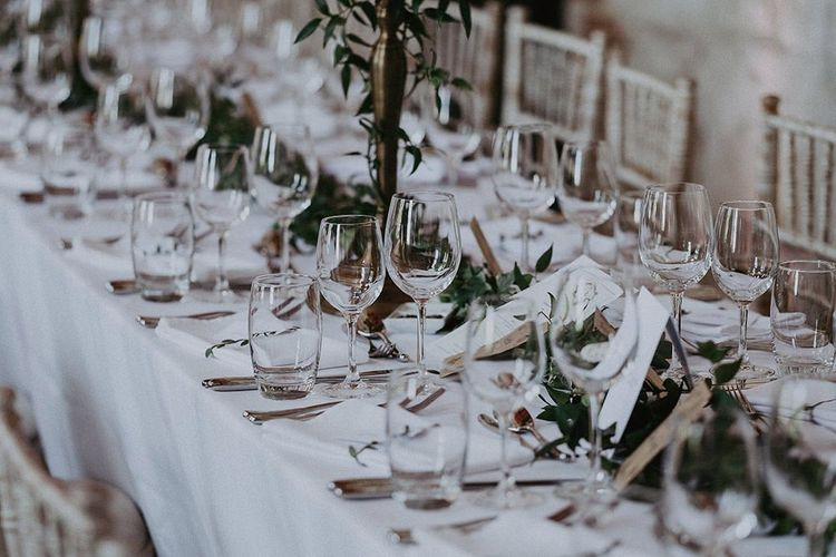 Table decor with candlestick centrepieces and green foliage