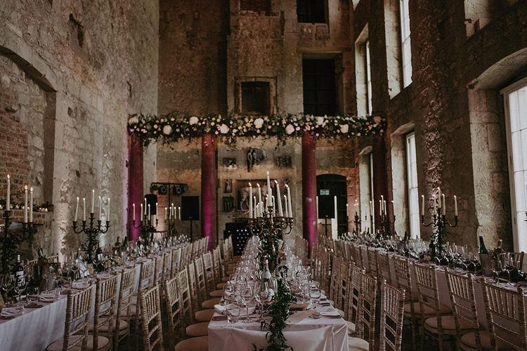 Wedding reception decor with candles and green foliage centre pieces