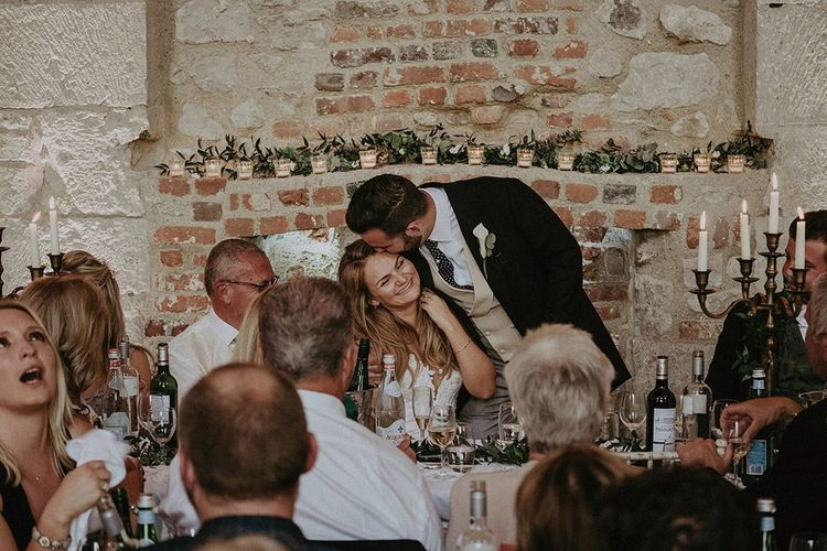Bride and groom enjoying the first speeches with exposed brick detailing ant candle stick centre pieces