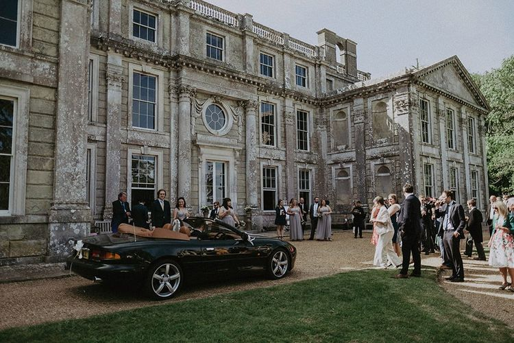 Guests arriving at Appuldurcombe House for wedding reception with bride wearing lace edge veil