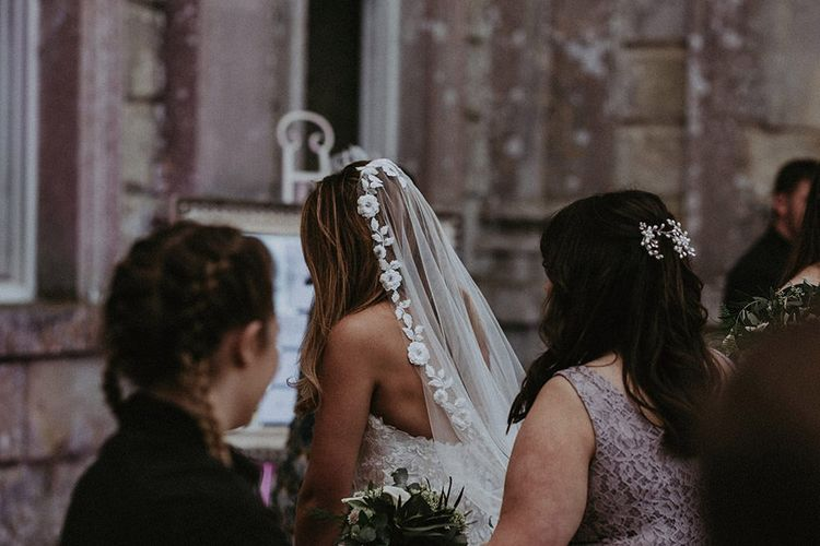Bride wearing a beautiful lace edge veil arrives at the wedding reception