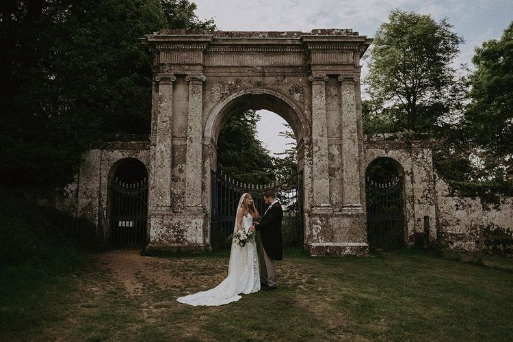 Bride and groom steal a moment next to ruins at Appuldurcombe House wearing lace edge veil