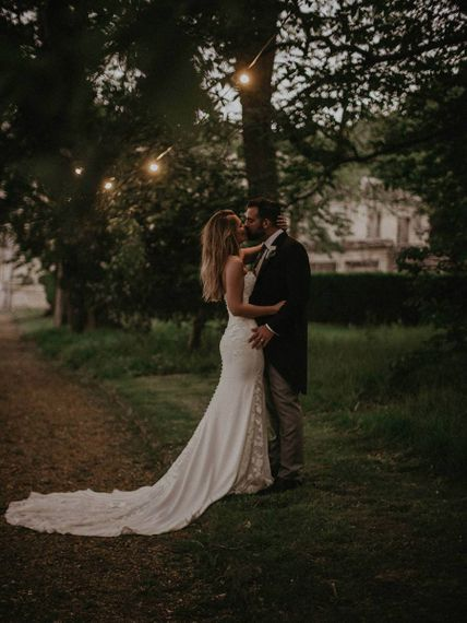 Bide and groom embrace in the grounds of Appuldurcombe House with fairy lights in the trees