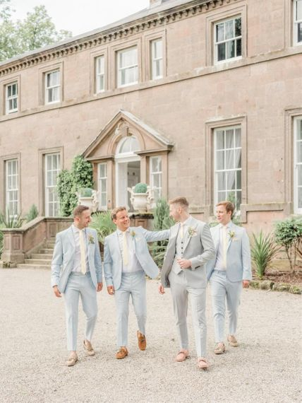 Groomsmen In Grey Suits in Front Of The Wedding Venue for Marble Wedding Cake Wedding