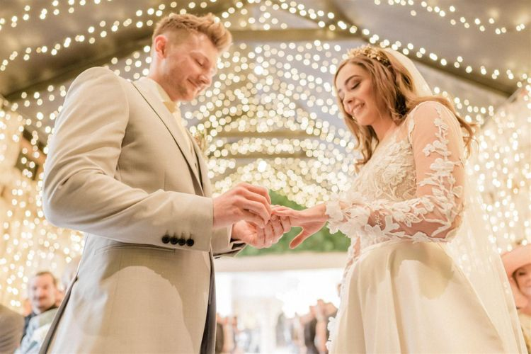 Bride and Groom Exchanging Rings Under Fairy Light Canopy