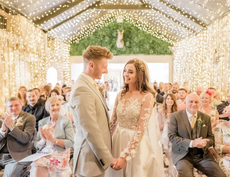Bride and Groom Holding Hands at the Wedding Ceremony With Fairy Lights