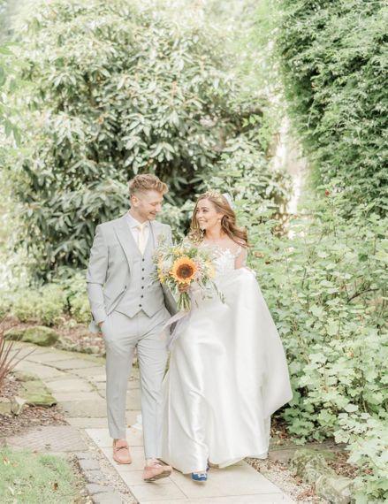 Bride and Groom Walk Through Venue Grounds Holding Sunflower Wedding Bouquet
