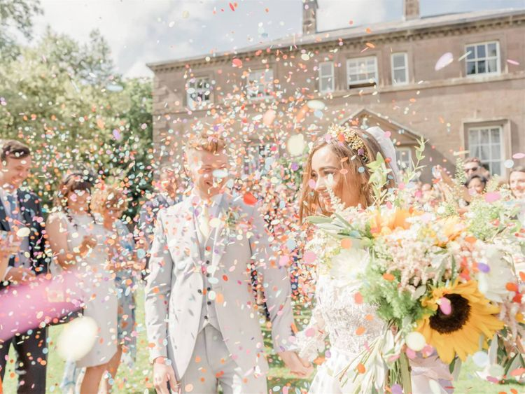 Colourful Confetti Moment with Groom in Grey suit and Bride in Emma Beaumont Wedding Dress