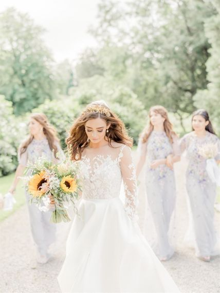 Bride In Lace Emma Beaumont Wedding Dress with Long Sleeves Holding a Sunflower Bouquet