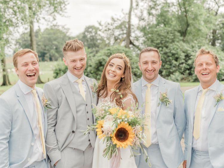 Bride Between Groom and Groomsmen In Grey and Blue Suits