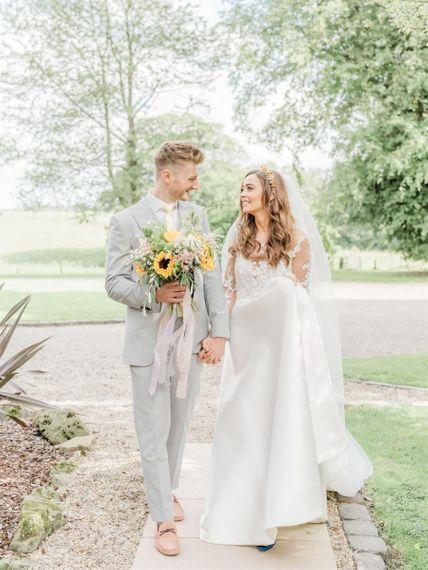 Bride in Emma Beaumont Wedding Dress and Groom in Grey Suit Walking Through Venue Grounds