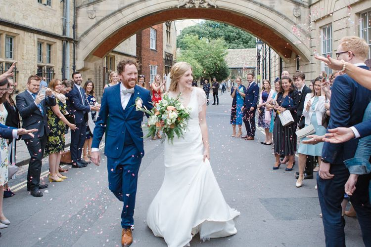 Confetti Moment with Bride in Sassi Holford Tamara Wedding Dress and Groom in Navy Blue Ted Baker Suit