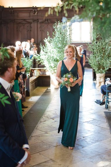 Bridesmaid Walking Down the Aisle in Forest Green Jenny Yoo Dress