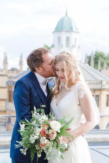 Groom in Navy Ted Baker Suit Kissing His Bride in Sassi Holford Tamara Wedding Dress