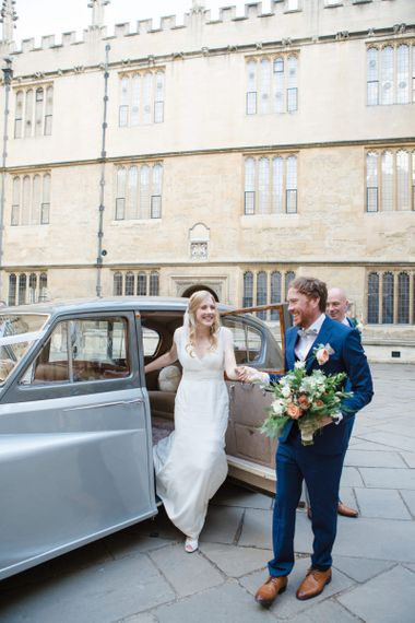 Groom in Navy Ted Baker Suit Helping His Bride in Sassi Holford Tamara Wedding Dress Out of The Wedding Car