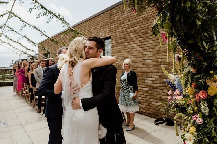 Bride and groom tie the knot at a private rooftop wedding in London with floral decor