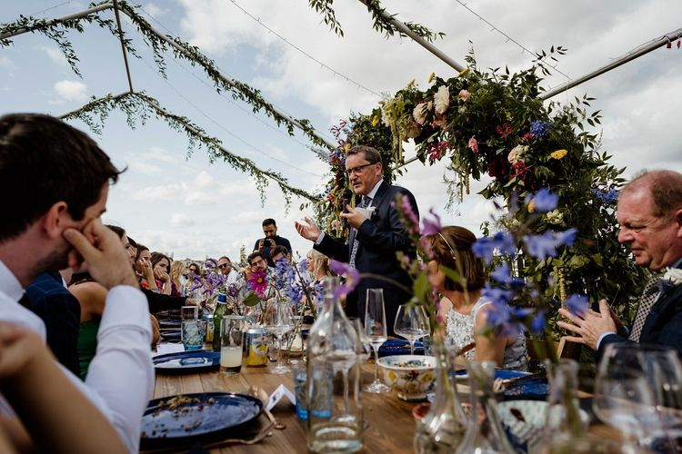 Toasts at outdoor wedding reception with hanging foliage and floral decor
