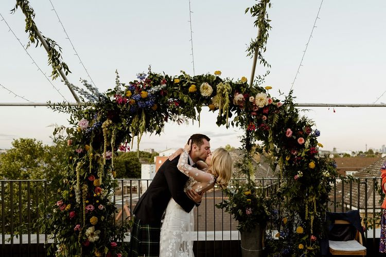 Bride and groom embrace at outdoor reception wearing beautiful bridal jumpsuit