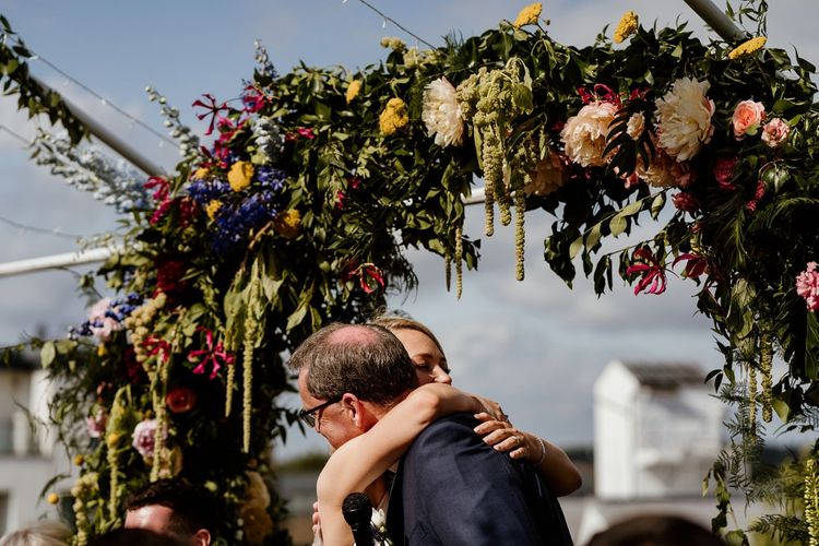 Bride hugs family member at outdoor wedding with floral decor
