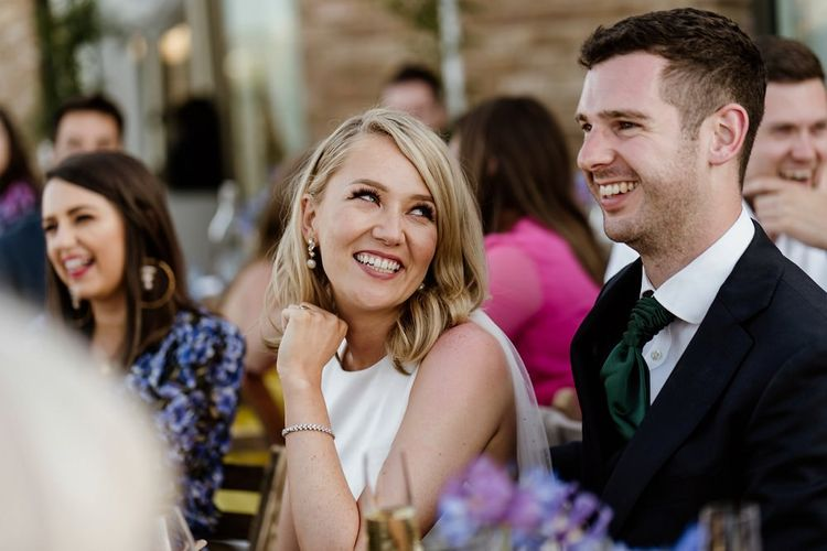 Bride and groom at outdoor wedding with bridal jumpsuit