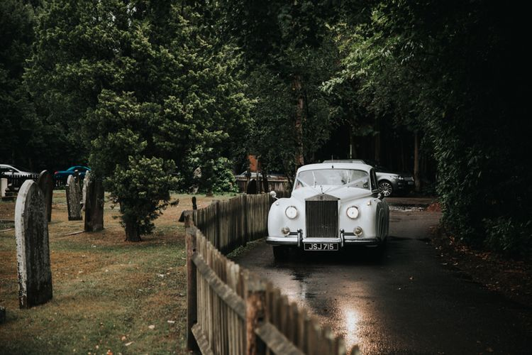 White vintage wedding car arriving at church ceremony