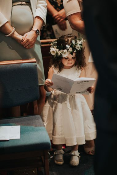 Cute flower girl in white dress and flower crown for church ceremony