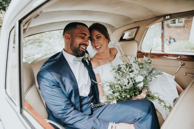Bride and groom in white wedding car make their way to Bury Court Barn