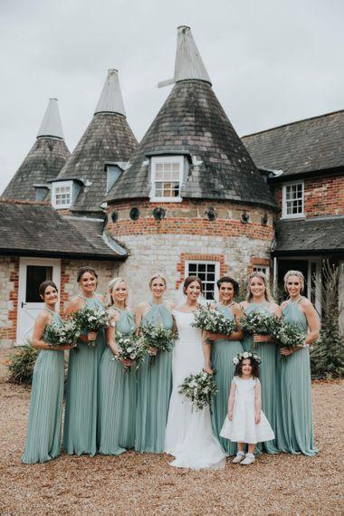 Bridesmaids in sage green dresses at Bury Court Barn