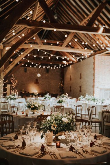 Festoon lighting drapes over wedding tables decorated in white flowers at Bury Court Barn