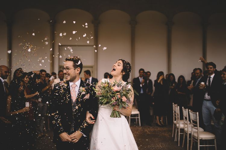 Bride and Groom Having Confetti Thrown Over Them