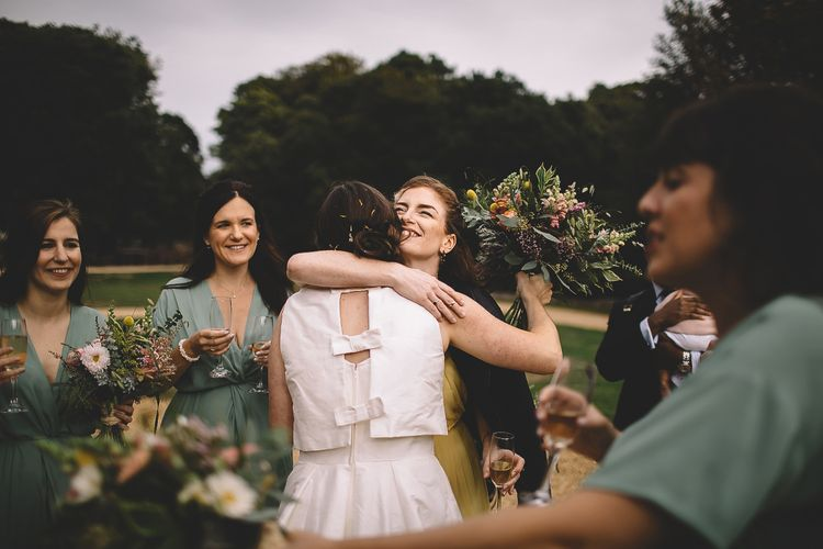Bride in Homemade Wedding Dress with Bow Back Hugging Wedding Guests