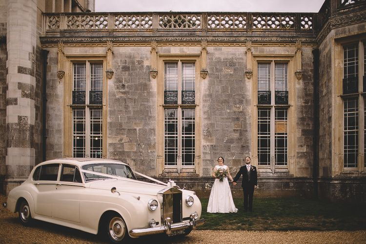 Bride and Groom Stnding in From top Their Castle Wedding Venue with Classic Wedding Car