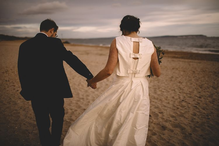 Bride in Homemade Wedding Dress with Bow Back and Groom in Dress2Kill Suit on the Beach
