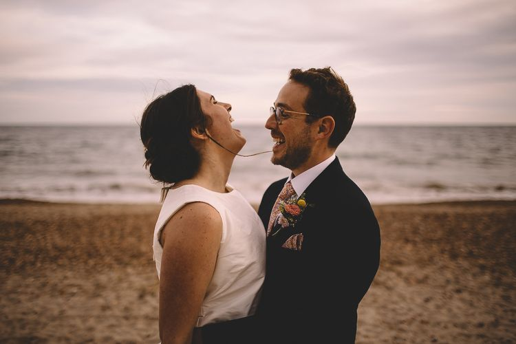 Bride in Homemade Wedding Dress with Bow Back and Groom in Dress2Kill Suit Laughing on the Beach