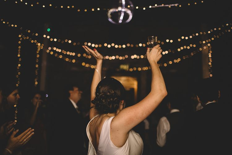 Bride in Homemade Wedding Dress with Bow Back Detail Dancing at Evening Reception with Fairylight Backdrop