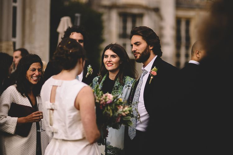 Bride in Homemade Wedding Dress with Bow Back Detail Talking to Wedding Guests