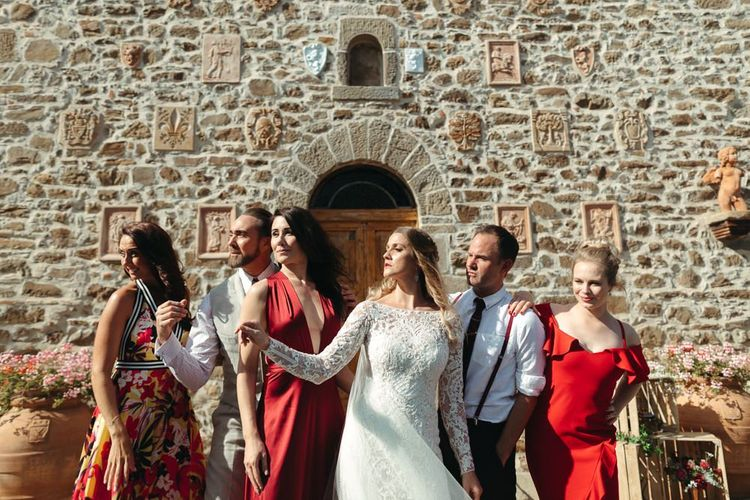 Bridal Party Portrait with Bride in Lace Wedding Dress and Bridesmaids in Different Coloured Red Dresses
