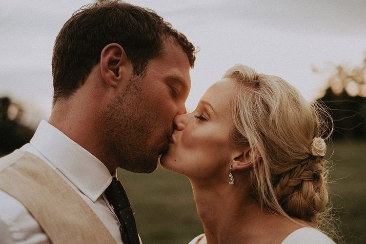Bride and Groom Share a Kiss with Bride's Hair In Low Braided Bun