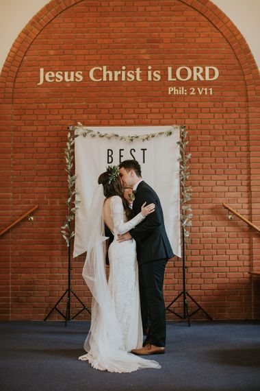 Church Wedding Ceremony with Bride and Groom Kissing in Front of a Best Day Ever Banner