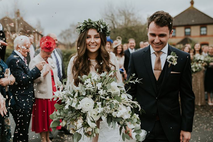 Confetti Moment with Boho Bride in Lace Wedding Dress and Flower Crown  with Groom in Moss Bros. Suit