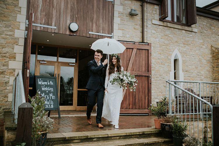Bride and Groom Exiting The Wedding Venue Under an Umbrella