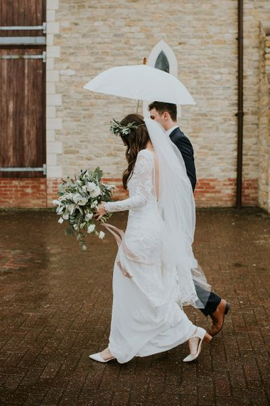 Bride Long Sleeve Grace Loves Lace Wedding Dress and Groom in Moss Bros. Suit Under and Umbrella
