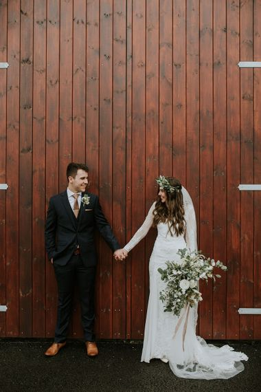 Bride Long Sleeve Grace Loves Lace Wedding Dress and Groom in Moss Bros. Suit Holding Hands