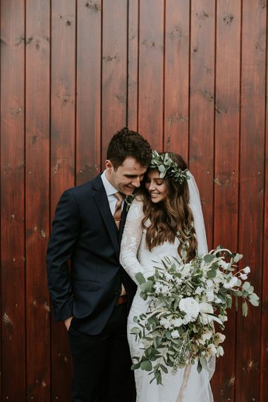 Bride Long Sleeve Grace Loves Lace Wedding Dress and Groom in Moss Bros. Suit Embracing