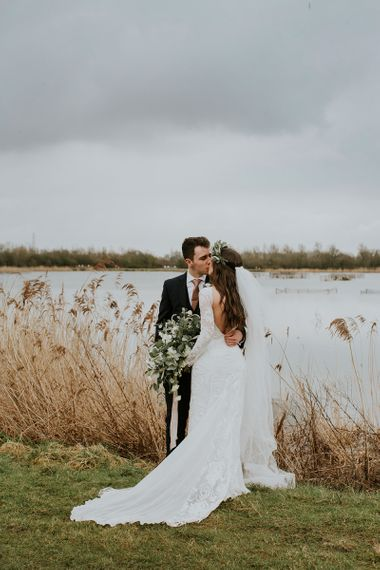 Bride in Long Sleeve and Backless Grace Loves Lace Wedding Dress and Groom in Moss Bros. Suit