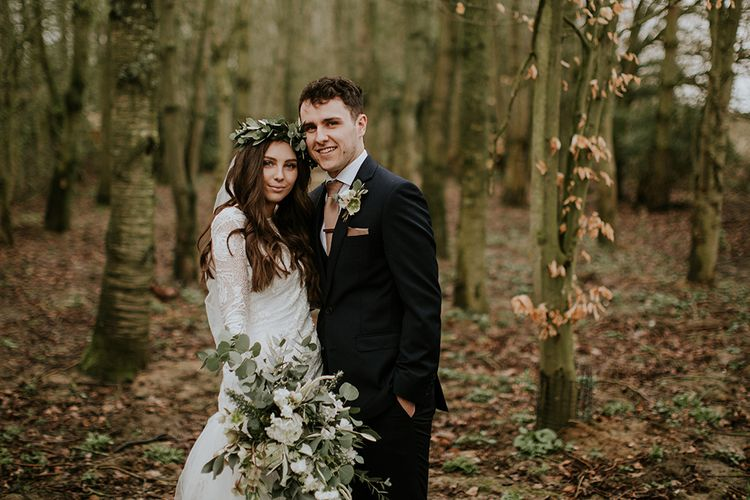 Bride in Long Sleeve and Backless Grace Loves Lace Wedding Dress and Groom in Moss Bros. Suit in the Woods