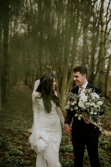Bride in Long Sleeve and Backless Grace Loves Lace Wedding Dress and Groom in Moss Bros. Suit Holding Hands in the Woods